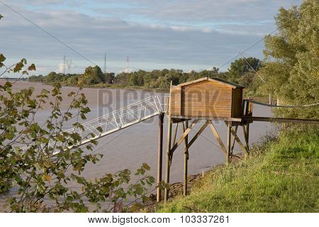 Wooden Home On Stilts Over Water Of The River