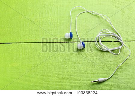 White Headphones On A Green Wooden Table