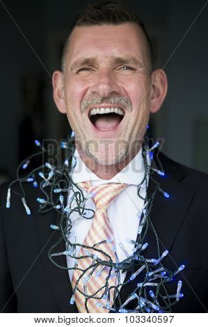 Portrait Of Man In Suit With String Lights And Laughing