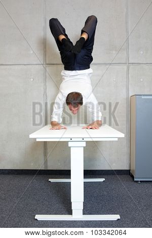 flexible business man in scorpion asana on desk in his office - front view