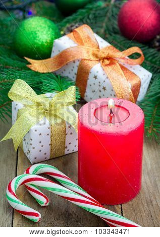 Christmas Composition With Gift Box, Candy Canes And Candle, Closeup