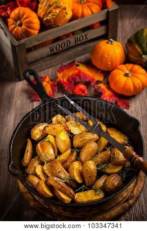 Rustic baked potatoes with herbs and pumpkins