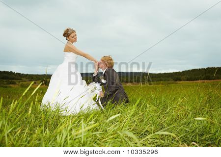 Groom Kisses Hand Of Bride In Field