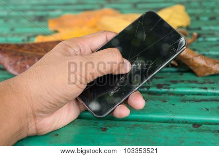 Hands holding and thump up touch on broken mobile smartphone sceen at outdoor park