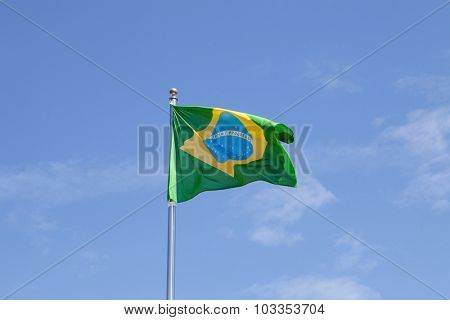 Brazilian flag waving in the mast with blue sky background