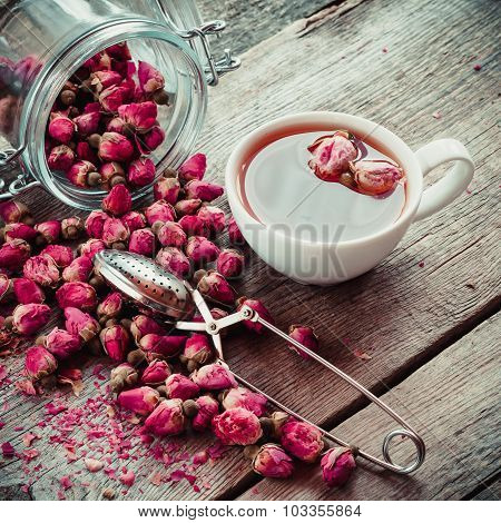 Dry Rose Flowers, Tea Cup, Strainer And Glass Jar With Rose Buds. Selective Focus. Retro Styled Phot
