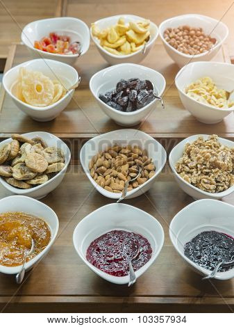 Cereals, nuts and jams in bowls on a wooden table at a hotel breakfast buffet
