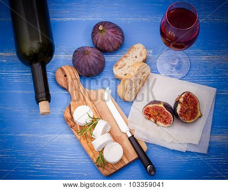 Goat Cheese With Ripe Figs And Wine On Blue