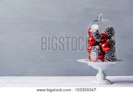 Modern simplistic minimalist christmas table display with pine cones and red baubles under a glass dome