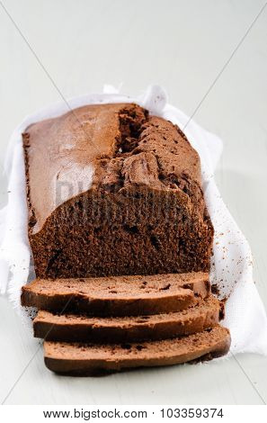 Loaf of chocolate cake with several slices wrapped with muslin cloth