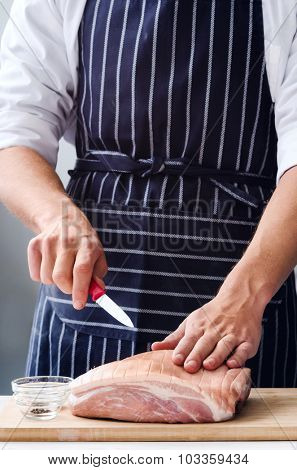 Butcher chef hands preparing to cut raw meat pork, cooking preparation on the table