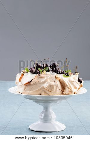 Pavlova garnished with cherries, mint and nuts, traditionally Australian dessert similar to a meringue