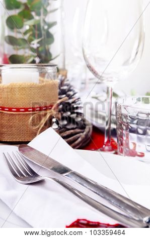 Christmas table place setting with wine glasses in red and white with pine cones, candles and leaf centerpiece