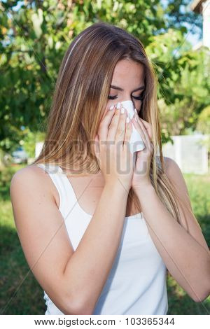 Teenage girl blowing nose outdoors