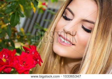 Close-up shot of a young girl smelling red rose