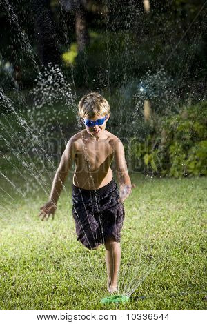 Boy Running Through Lawn Sprinkler