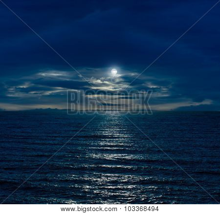 Night sky with full moon and reflection in sea and clouds