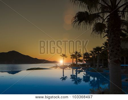 Sunset in a tropical island with pool and sea