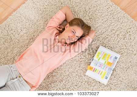 Woman With Diary Lying On Carpet