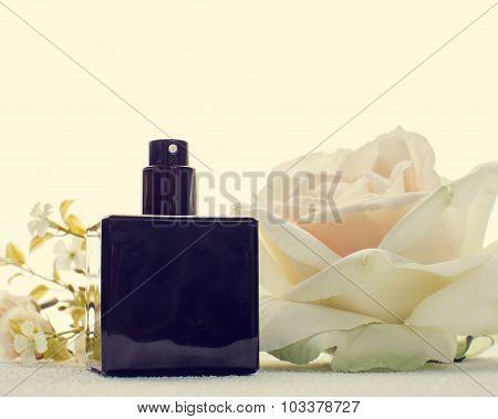 Black Perfume Bottle And White Flower