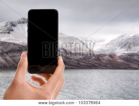 Hand holding mobile with black screen with Glacier Bay on background