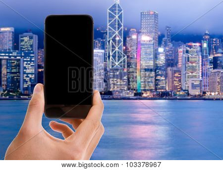 Hand holding mobile with black screen on Hong Kong background
