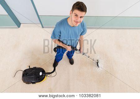 Male Janitor Vacuuming Corridor