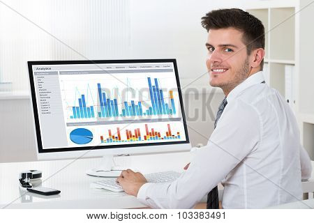 Businessman Analyzing Financial Report On Computer
