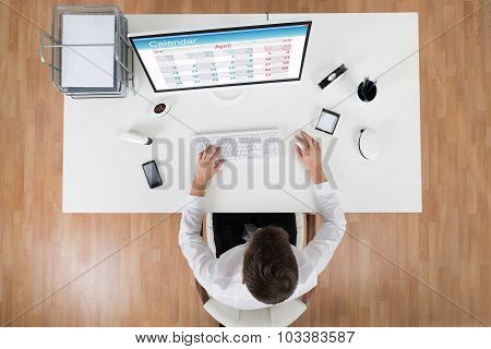 Young Businessman Looking At Calendar On Computer