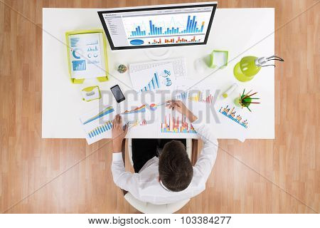 Businessman Analyzing Graph On Computer At Desk