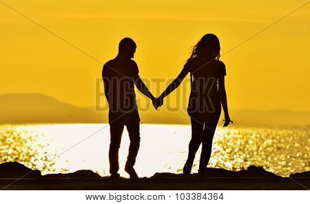 Young couple walking hand to hand over sunset