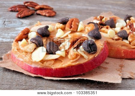 Apple rounds close up with peanut butter, chocolate and nuts