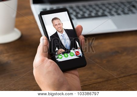 Person Videochatting With Colleague On Mobile Phone