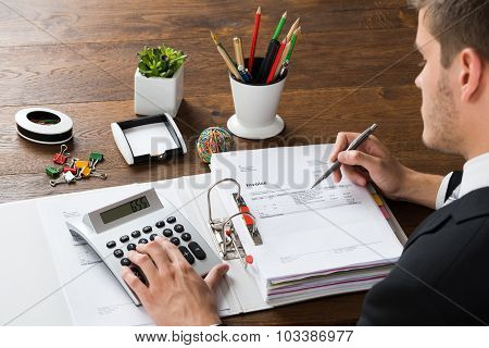 Businessman Calculating Receipt At Desk
