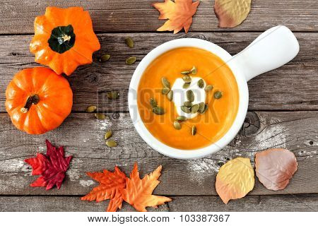 Autumn butternut squash soup on rustic wood background