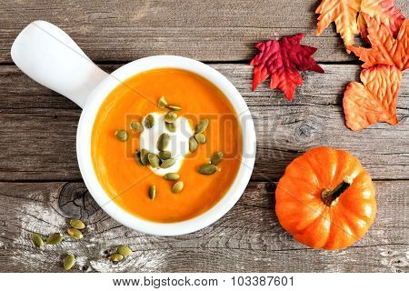 Creamy pumpkin soup on rustic wood background
