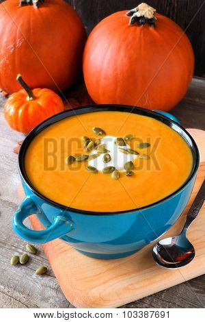 Autumn soup in blue bowl with pumpkins in background