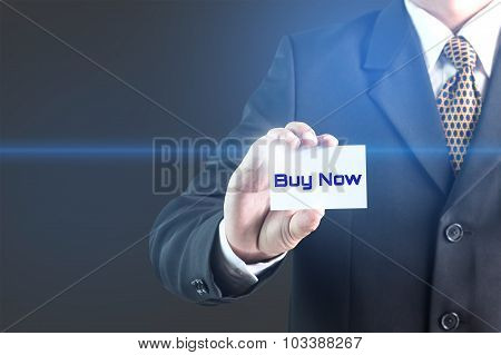 A Businessman holding a white sign with the message buy now.