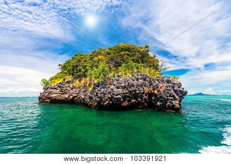 Big rock with trees and bushes in clear sea water. Perfect resort background