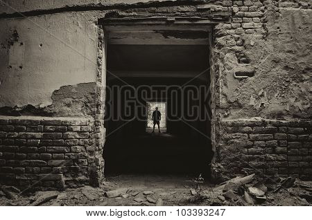 Silhouette Of The Man Standing At The End Of Dark Corridor Of Abandoned Building