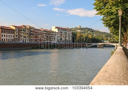 Buildings along the River Adige with the Ponte Garibaldi bridge and Sanctuary of the Madonna of Lourdes visible on the San Leonardo hill in Verona, Italy