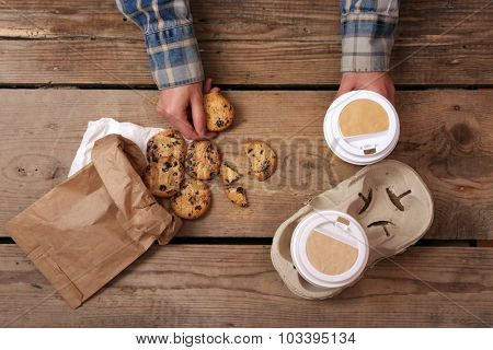 Female hands holding cup of coffee and cookies on wooden table close up