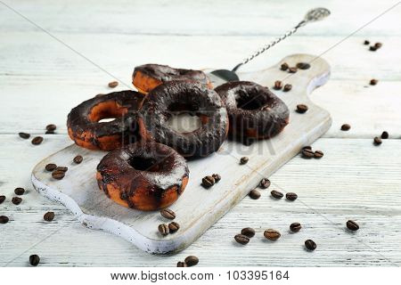 Delicious doughnuts with chocolate icing and coffee beans on table close up