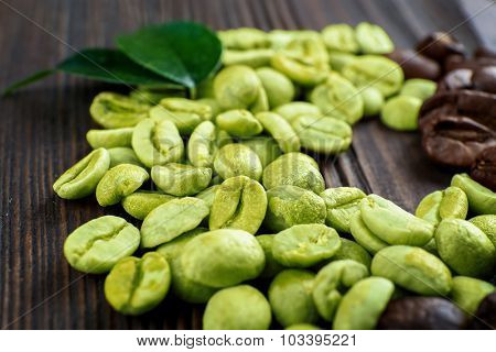Green and brown coffee beans with leaves on wooden table close up