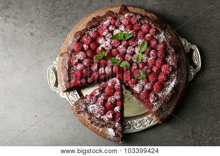 Cake with Chocolate Glaze and raspberries on tray on dark background