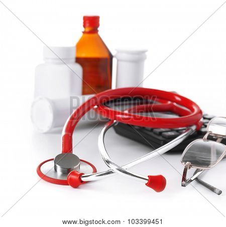 Medical stethoscope with bottles of pills and calculator isolated on white