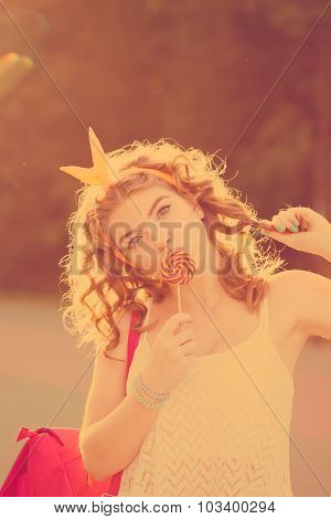Pin-up Girl Licking A Lollipop And Straightens Her Hair.
