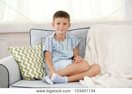 Little boy sitting on sofa, on home interior background