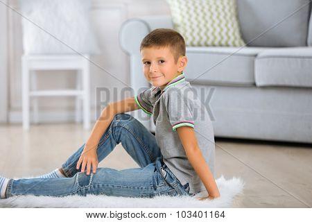 Little boy sitting on carpet, on home interior background
