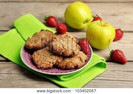 Homemade cookies with strawberries and apples on table close up